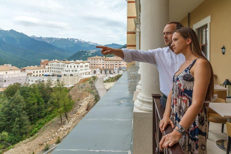 Unga lyckliga Caucasian par som tillsammans tycker om ett sceniskt anseende för sommarbergsikt på restaurangs terrass av gamlan S arkivfoto