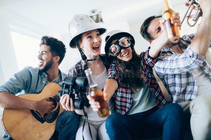 Unga lyckliga dansflickor som spelar gitarren och att festa royaltyfri bild
