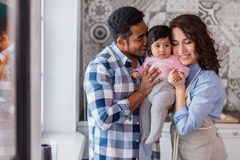 Unga lyckliga föräldrar som tycker om tid med deras, behandla som ett barn royaltyfria bilder