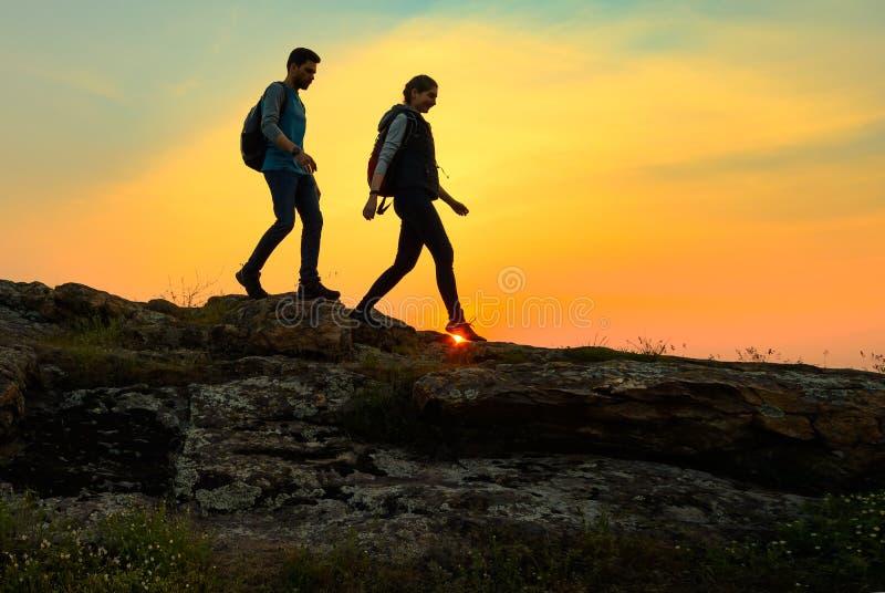 Unga lyckliga handelsresande som fotvandrar med ryggs?ckar p? Rocky Trail p? sommarsolnedg?ngen Familjlopp- och aff?rsf?retagbegr arkivfoton