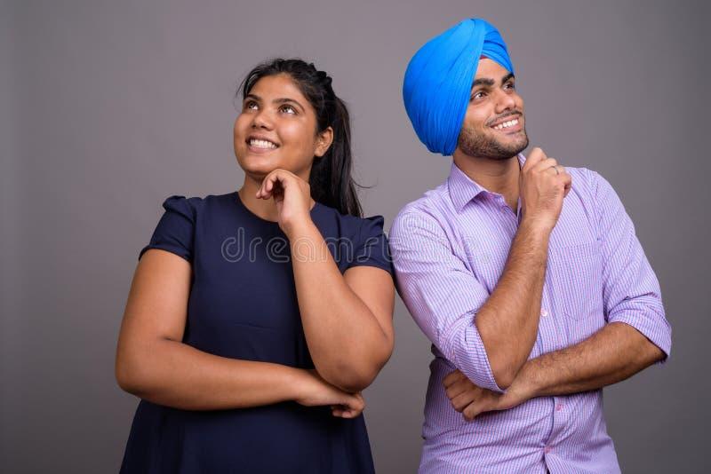 Unga lyckliga indiska par som tänker och upp ser tillsammans royaltyfri foto
