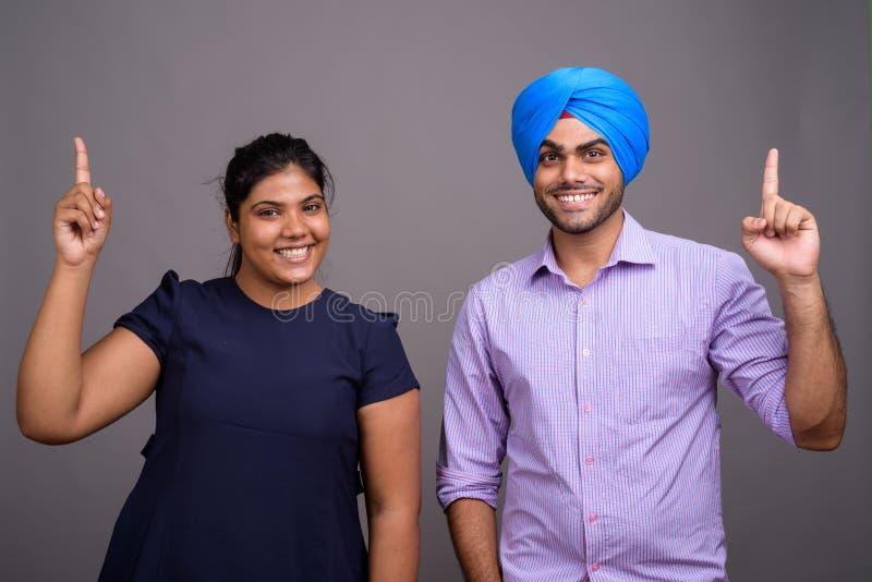 Unga lyckliga indiska par tillsammans och förälskat peka finger upp royaltyfri bild