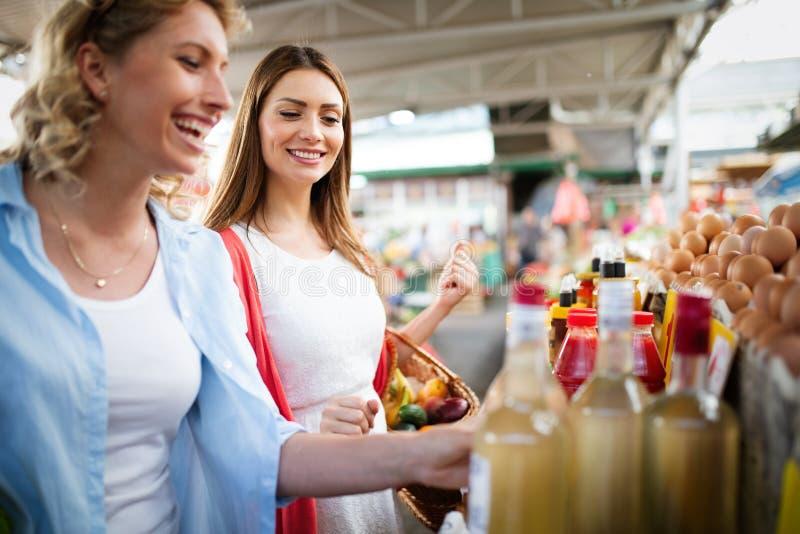 Unga lyckliga kvinnashoppinggrönsaker och frukter på marknaden royaltyfri bild
