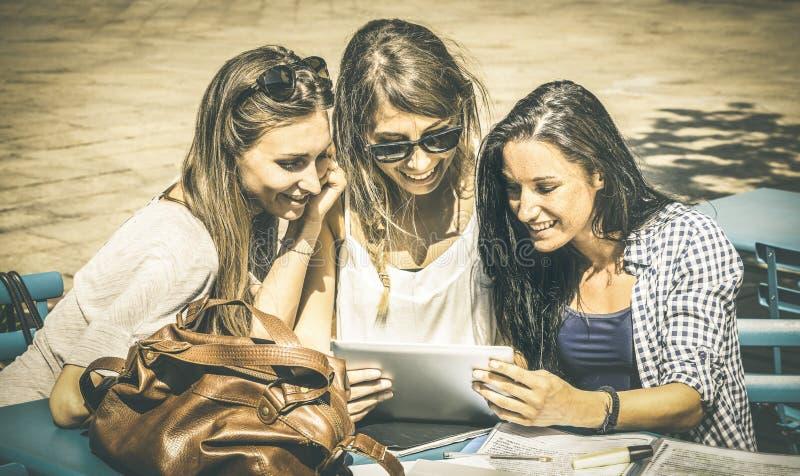 Unga lyckliga kvinnor som studerar och har gyckel samman med minnestavlan royaltyfria bilder