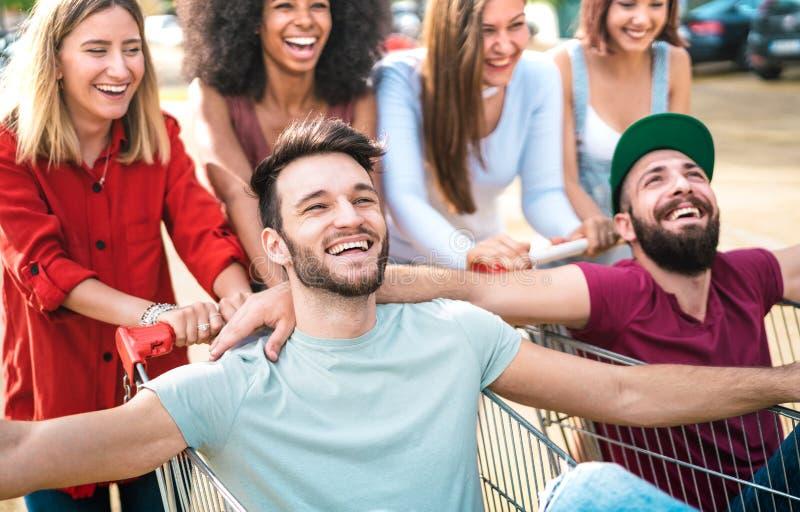 Unga lyckliga människor som har roligt tillsammans på shoppingvagnarna - Multietniska vänner som delar roligt med trådar på köpce royaltyfri bild