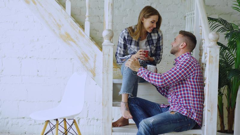 Unga lyckliga och älska par dricker te och samtal, medan sitta på trappa i vardagsrum hemma royaltyfria bilder