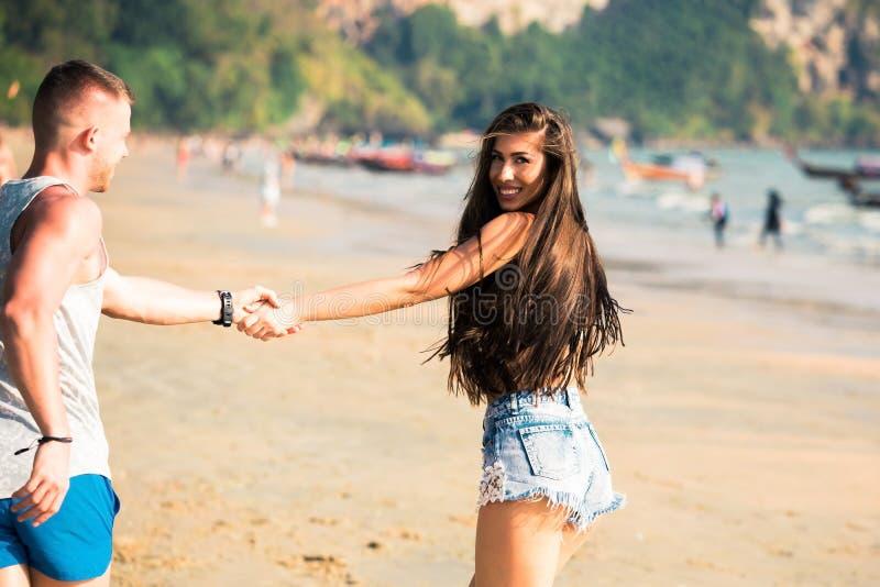 Unga lyckliga och glade Caucasian vuxna romantiska par som tillsammans kör och går, medan rymma händer i sommarkläder på tropiskt arkivbild