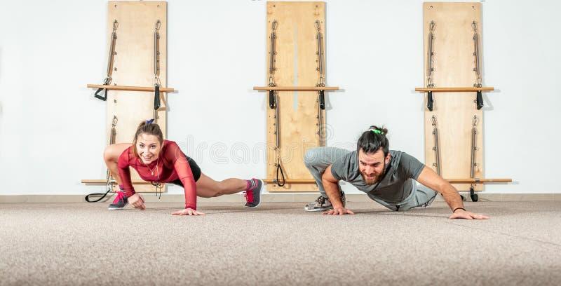 Unga lyckliga och sunda förälskade konditionpar ha gyckel med yogaövningar och genomkörare i den selektiva fokusen för idrottshal arkivbild