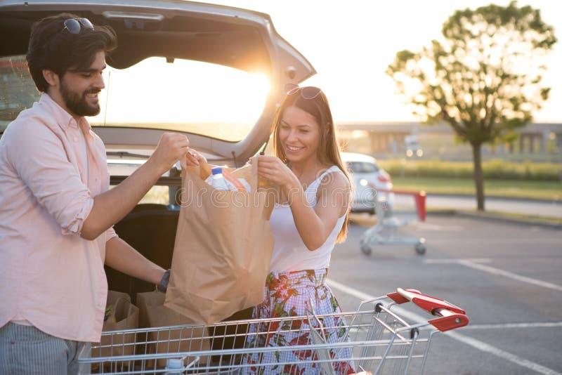 Unga lyckliga par framme av en supermarket i parkeringsplatsen arkivbild