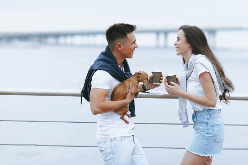 Unga lyckliga par går på med den lilla hunden på havspromenad arkivbild