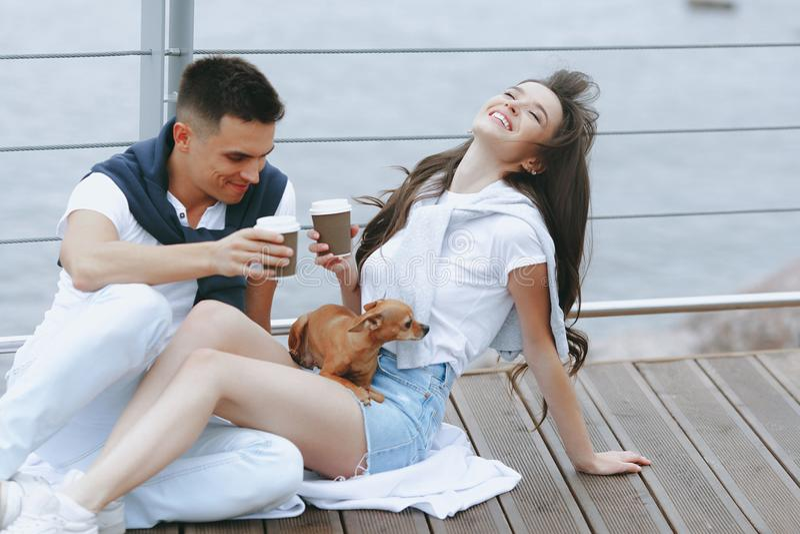 Unga lyckliga par går på med den lilla hunden på havspromenad royaltyfri bild