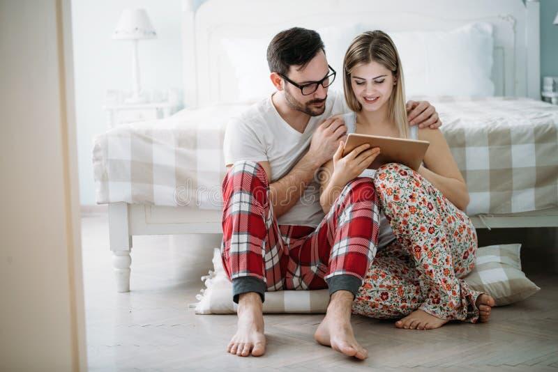 Unga lyckliga par genom att använda minnestavlan i sovrum royaltyfri bild