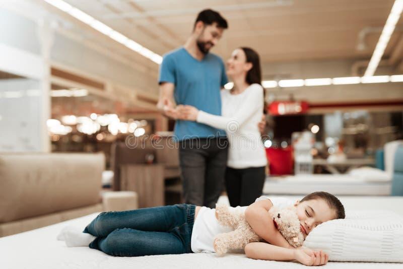 Unga lyckliga par i bakgrund som tycker om sova lilla flickan Välja madrassen i lager royaltyfria foton