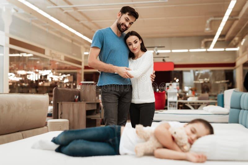 Unga lyckliga par i bakgrund som tycker om sova lilla flickan Välja madrassen i lager arkivbild