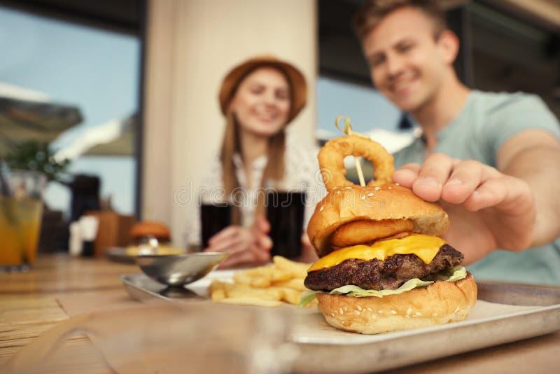 Unga lyckliga par i gatakafét, fokus på mannen som tar den smakliga hamburgaren arkivfoto