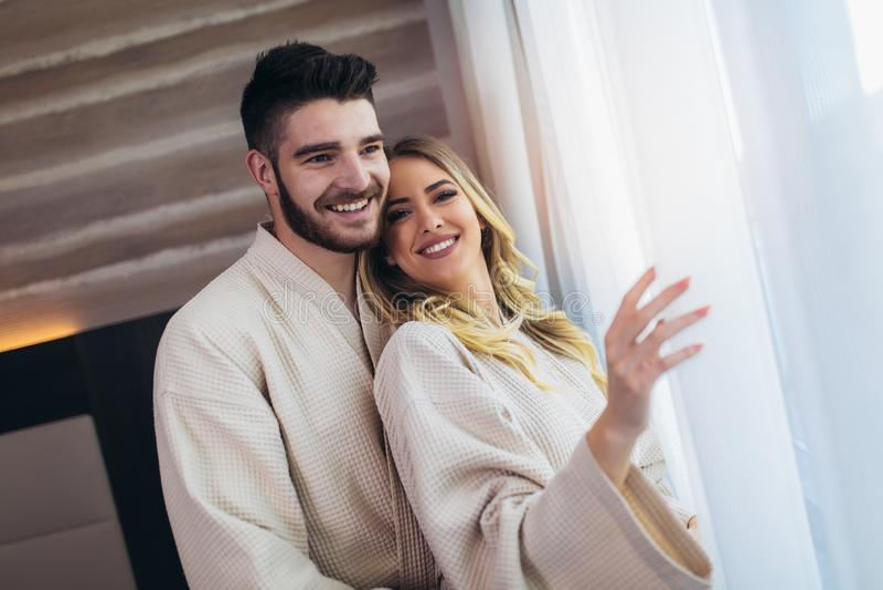 Unga lyckliga par i hotellrum i morgonen royaltyfri fotografi