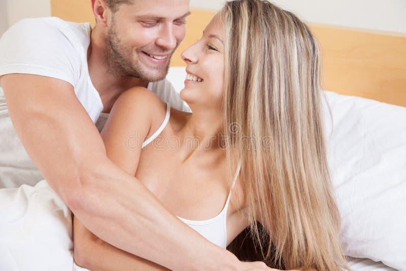 Unga lyckliga par i säng arkivfoton
