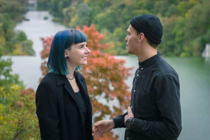 Unga lyckliga par i svarta skjortor som talar på flod- och skogbakgrund royaltyfri bild