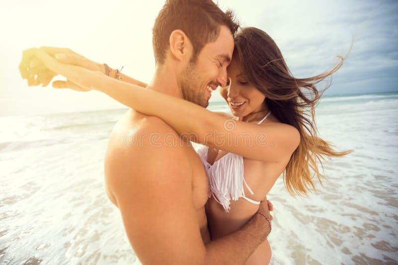 Unga lyckliga par med attraktionhjärta på den tropiska stranden royaltyfri bild