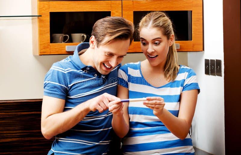 Unga lyckliga par med graviditetstestanseende i kök arkivbilder