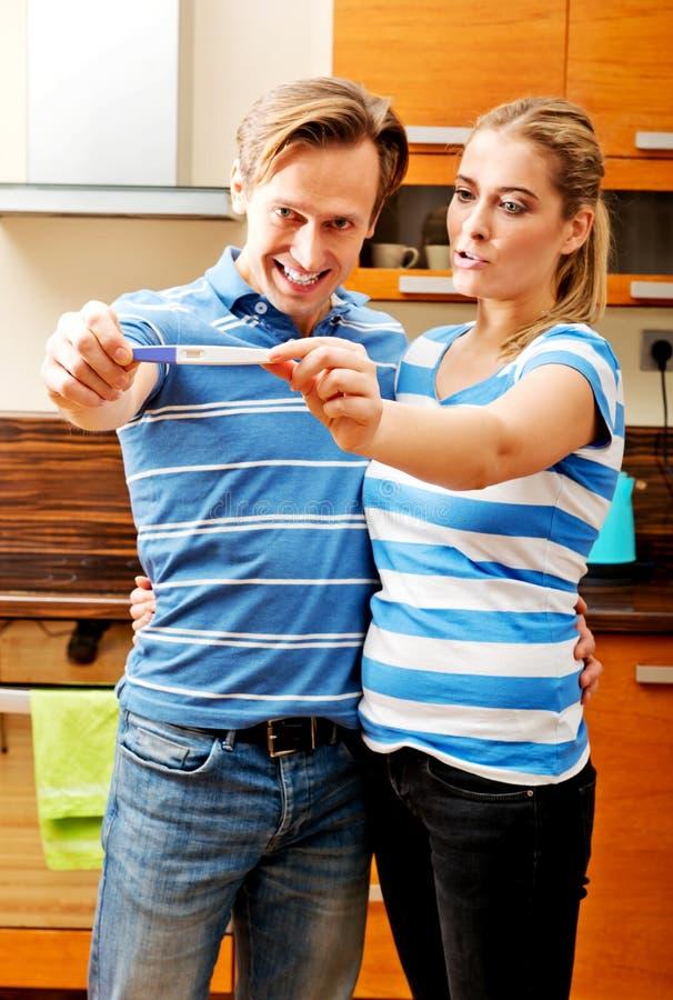 Unga lyckliga par med graviditetstestanseende i kök royaltyfria bilder