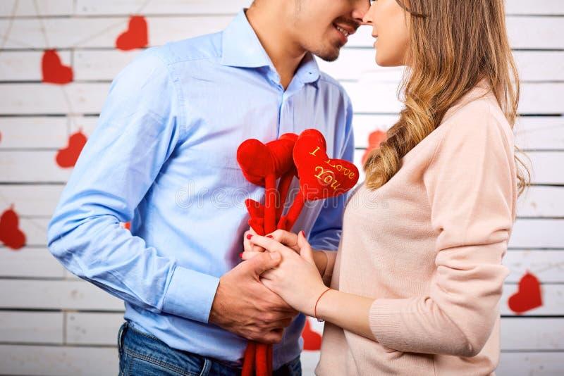 Unga lyckliga par med hjärta i handonbackground arkivbilder