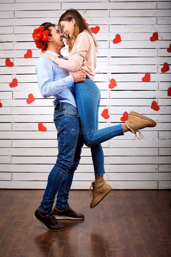 Unga lyckliga par med hjärta i handonbackground arkivfoto