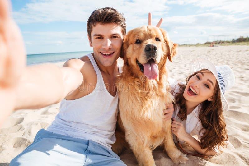 Unga lyckliga par med hunden som tar en selfie arkivbild