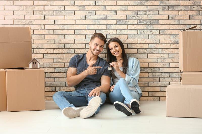Unga lyckliga par med tangenten och rörande askar som sitter på golv på det nya hemmet royaltyfria bilder