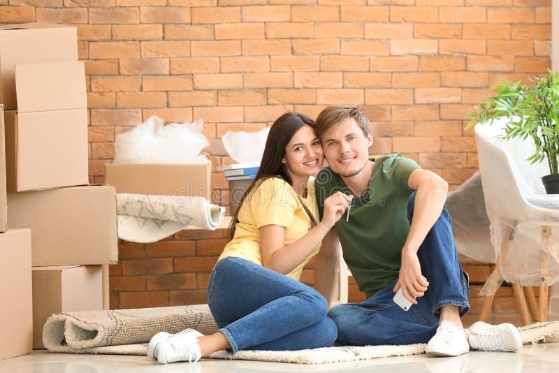 Unga lyckliga par med tangenten och rörande askar som sitter på matta på det nya hemmet royaltyfri bild