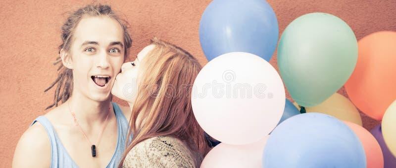 Unga lyckliga par nära den orange väggen står med ballonger arkivfoto
