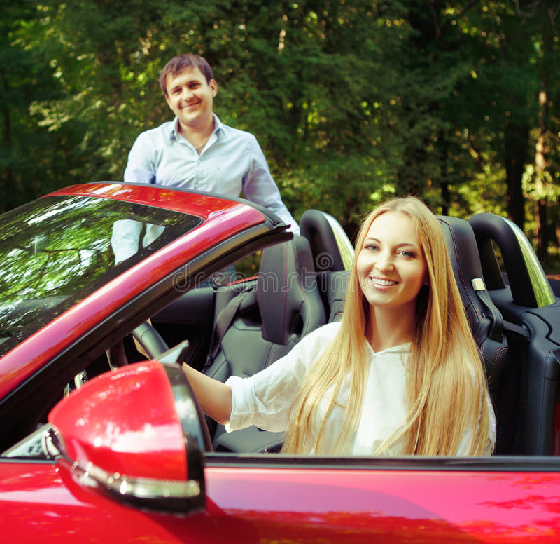 Unga lyckliga par nära den röda bilen arkivfoton