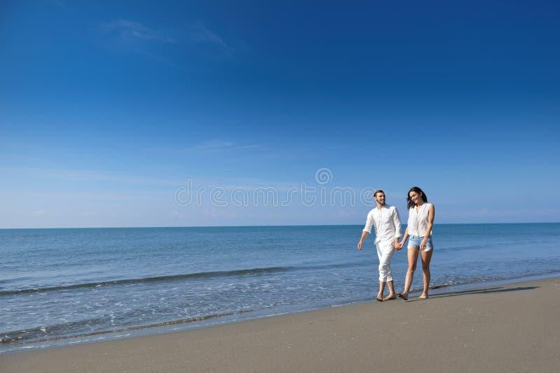 Unga lyckliga par på den vita stranden på sommarsemestern arkivfoton