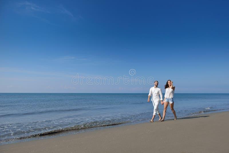 Unga lyckliga par på den vita stranden på sommarsemestern royaltyfri foto
