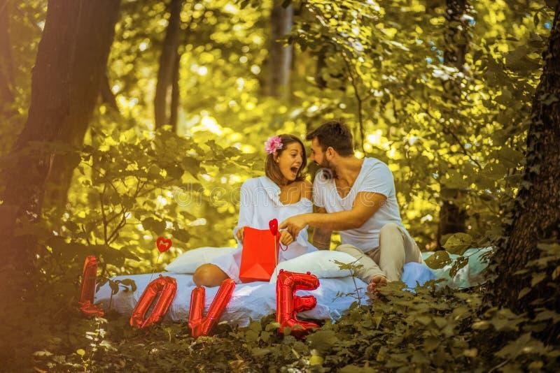 Unga lyckliga par på naturen Fira årsdagen royaltyfria bilder
