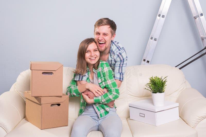 Unga lyckliga par på Sofa Taking ett avbrott från uppackning på rörande dag royaltyfria foton