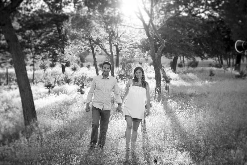 Unga lyckliga par som är förälskade på, parkerar tillsammans landskapsolnedgång med den gravida buken för kvinnan fotografering för bildbyråer
