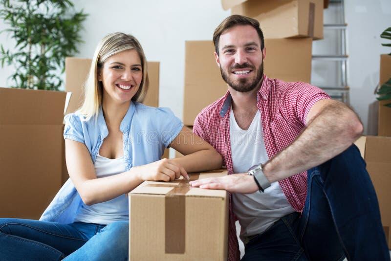 Unga lyckliga par som firar att flytta sig till det nya hemmet royaltyfria bilder