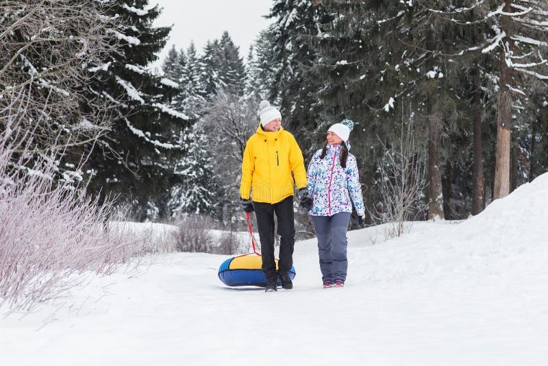 Unga lyckliga par som går i vinter, parkerar arkivfoto