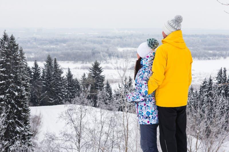 Unga lyckliga par som går i vinter, parkerar fotografering för bildbyråer