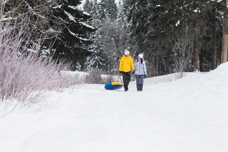 Unga lyckliga par som går i vinter, parkerar arkivfoton