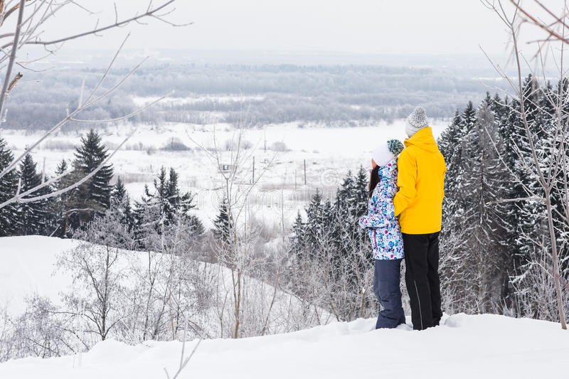 Unga lyckliga par som går i vinter, parkerar royaltyfria bilder