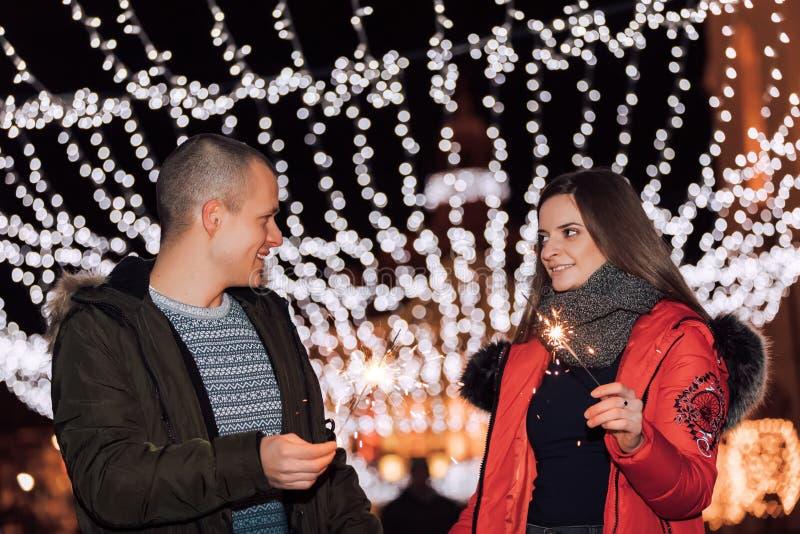 Unga lyckliga par som har gyckel med tomtebloss på vinteraftonen royaltyfria foton