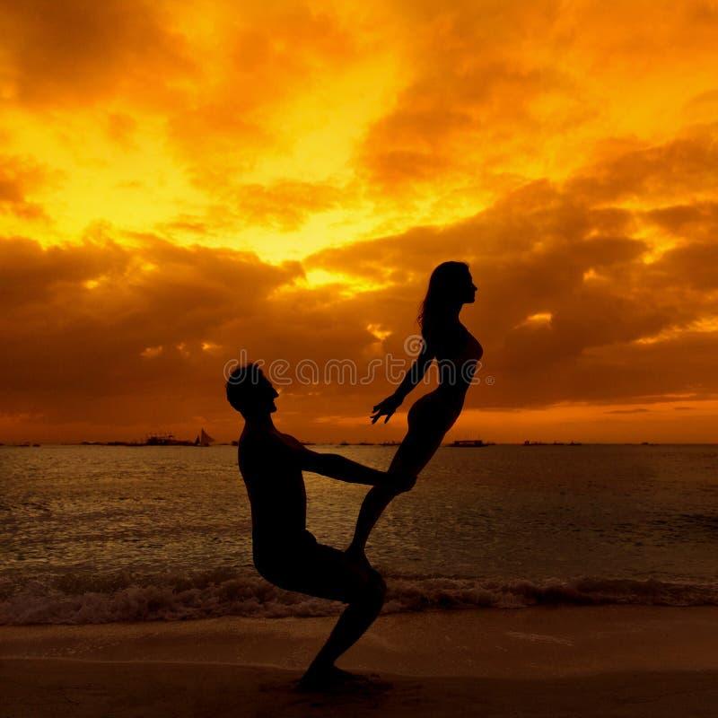 Unga lyckliga par som har gyckel på en tropisk strand med sunsen royaltyfria bilder