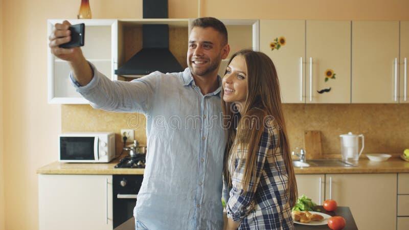 Unga lyckliga par som har online-video pratstund i köket hemma arkivfoto