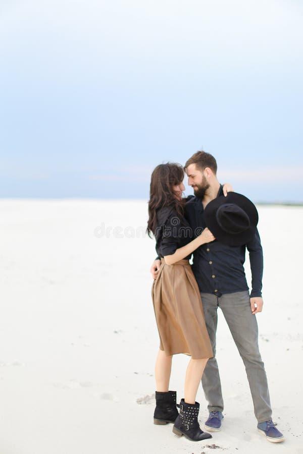 Unga lyckliga par som kramar i monophonic bakgrund för vintersnö, bärande kjol och svartskjorta royaltyfri fotografi