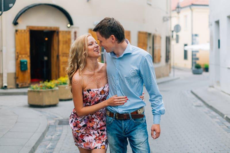 Unga lyckliga par som kramar, medan gå på gatan arkivfoto