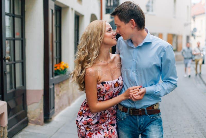 Unga lyckliga par som kramar, medan gå på gatan arkivfoton