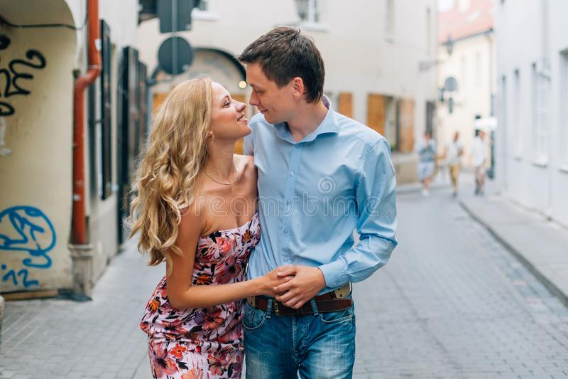 Unga lyckliga par som kramar, medan gå på gatan royaltyfria foton