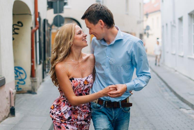 Unga lyckliga par som kramar, medan gå på gatan arkivbild